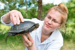 Αρκετά ξανθή γυναίκα που κρατά μια χελώνα Στοκ Φωτογραφία