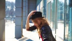 Αρκετά ξανθή γυναίκα στα βήματα καπέλων έξω από τη στήλη και τους χορούς στο φως ήλιων απόθεμα βίντεο