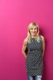 Αρκετά ξανθή γυναίκα στην καθιερώνουσα τη μόδα εξάρτηση ενάντια στο ροζ Στοκ Εικόνες
