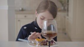 Αρκετά ξανθή συνεδρίαση κοριτσιών στον πίνακα στην κουζίνα που τρώει το κέικ με τα δάχτυλά της, υψηλό γυαλί με το χυμό που στέκετ απόθεμα βίντεο