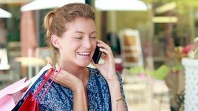 Αρκετά ξανθή τσάντα αγορών εκμετάλλευσης και κατοχή του τηλεφωνήματος φιλμ μικρού μήκους