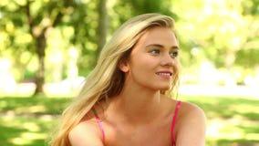 Αρκετά ξανθή χαλάρωση στο πάρκο και χαμόγελο στη κάμερα απόθεμα βίντεο