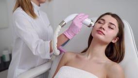 Αρκετά ξανθός γιατρός beautician που κάνει τη διαδικασία RF-ανύψωσης για την τοποθέτηση γυναικών σε ένα σαλόνι ομορφιάς r φιλμ μικρού μήκους