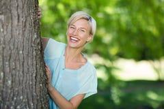 Αρκετά ξανθός που κρύβεται πίσω από ένα δέντρο Στοκ εικόνα με δικαίωμα ελεύθερης χρήσης