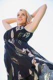 Αρκετά ξανθός στα sundress που στέκονται με τα όπλα πίσω από το κεφάλι Στοκ Φωτογραφία