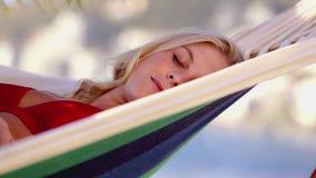 Αρκετά ξανθός ύπνος γυναικών σε μια αιώρα απόθεμα βίντεο