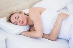 Αρκετά ξανθός ύπνος γυναικών στο κρεβάτι Στοκ εικόνα με δικαίωμα ελεύθερης χρήσης