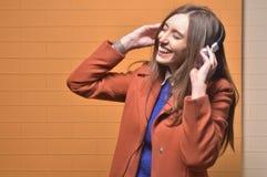 Αρκετά ξανθό κορίτσι που γελά ενώ μουσική ακούσματος στοκ φωτογραφία με δικαίωμα ελεύθερης χρήσης