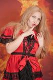 αρκετά ξανθό κορίτσι στο κόκκινο φόρεμα παραμυθιού που στέκεται στο πορτοκαλί υπόβαθρο με τα αστέρια στοκ εικόνες