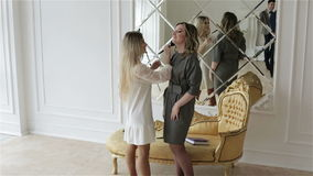 Αρκετά οι νεολαίες αποτελούν τον καλλιτέχνη εργάζονται με το πρότυπο κοντά στο μεγάλο καθρέφτη και το χρυσό καναπέ απόθεμα βίντεο
