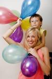 Αρκετά πραγματική οικογένεια με τα μπαλόνια χρώματος στο άσπρο υπόβαθρο, ξανθή γυναίκα με το μικρό παιδί στο φωτεινό χαμόγελο γιο Στοκ εικόνες με δικαίωμα ελεύθερης χρήσης