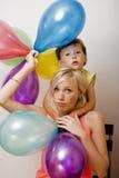 Αρκετά πραγματική οικογένεια με τα μπαλόνια χρώματος στο άσπρο υπόβαθρο, ξανθή γυναίκα με το μικρό παιδί στο φωτεινό χαμόγελο γιο Στοκ Φωτογραφίες