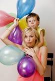 Αρκετά πραγματική οικογένεια με τα μπαλόνια χρώματος στο άσπρο υπόβαθρο, ξανθή γυναίκα με το μικρό παιδί στο φωτεινό χαμόγελο γιο Στοκ Εικόνες