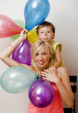 Αρκετά πραγματική οικογένεια με τα μπαλόνια χρώματος στο άσπρο υπόβαθρο, ξανθή γυναίκα με το μικρό παιδί στο φωτεινό χαμόγελο γιο Στοκ εικόνα με δικαίωμα ελεύθερης χρήσης