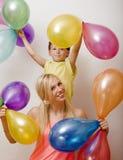 Αρκετά πραγματική οικογένεια με τα μπαλόνια χρώματος στο άσπρο υπόβαθρο, ξανθή γυναίκα με το μικρό παιδί στο φωτεινό χαμόγελο γιο Στοκ φωτογραφίες με δικαίωμα ελεύθερης χρήσης