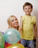 Αρκετά πραγματική οικογένεια με τα μπαλόνια χρώματος στο άσπρο υπόβαθρο, ξανθή γυναίκα με το μικρό παιδί στο φωτεινό χαμόγελο γιο Στοκ φωτογραφία με δικαίωμα ελεύθερης χρήσης