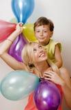 Αρκετά πραγματική οικογένεια με τα μπαλόνια χρώματος στο λευκό Στοκ Εικόνες