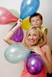 Αρκετά πραγματική οικογένεια με τα μπαλόνια χρώματος στο λευκό Στοκ Φωτογραφία