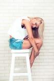 Αρκετά προκλητική νέα γυναίκα με την ξανθή τρίχα στην καρέκλα Στοκ Εικόνες