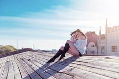 Αρκετά προκλητική συνεδρίαση γυναικών στην ξύλινη στέγη με τον ουρανό Στοκ Εικόνα