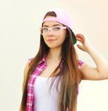 Αρκετά δροσερό κορίτσι που φορά ένα ρόδινο καπέλο του μπέιζμπολ και ρόδινα γυαλιά Στοκ εικόνα με δικαίωμα ελεύθερης χρήσης