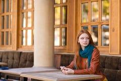 Αρκετά στοχαστική συνεδρίαση γυναικών στον πίνακα στον υπαίθριο καφέ στοκ εικόνα
