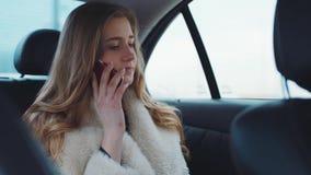 Αρκετά συμπαθητικό ξανθό κορίτσι που μιλούν με το φίλο στο τηλέφωνό της και οδηγώντας σπίτι χαμόγελου σε ένα σύγχρονο αυτοκίνητο  απόθεμα βίντεο