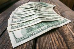 Αρκετά τραπεζογραμμάτια 100 δολαρίων semicircle στο σχεδιάγραμμα στο ηλικίας τραχύ ξύλινο windowsill στοκ φωτογραφία