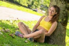 Αρκετά φίλαθλο κορίτσι που χαλαρώνει και που βρίσκεται στη χλόη Στοκ εικόνες με δικαίωμα ελεύθερης χρήσης