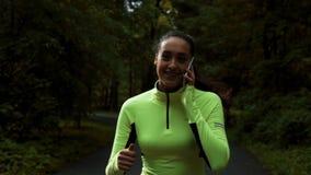 Αρκετά φίλαθλη γυναίκα που και που τρέχει στο πάρκο με το selfphone απόθεμα βίντεο
