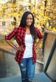 Αρκετά χαμογελώντας αφρικανική γυναίκα που φορά ένα κόκκινο ελεγμένο πουκάμισο Στοκ φωτογραφίες με δικαίωμα ελεύθερης χρήσης