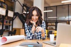 Αρκετά χαρούμενη νέα συνεδρίαση γυναικών στην ουσία εργασίας επιτραπέζιου πλαισίου Χαμογελώντας στη κάμερα, σχεδιασμός, που λειτο στοκ εικόνα με δικαίωμα ελεύθερης χρήσης