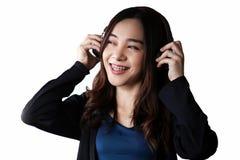 Αρκετά όμορφη ασιατική γυναίκα που φορά το ακουστικό και τη μουσική ακούσματος στο άσπρο υπόβαθρο στοκ φωτογραφία