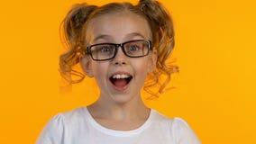 Αρκετά erudite κορίτσι στα γυαλιά που έχουν την ιδέα, κινηματογράφηση σε πρώτο πλάνο, απομονωμένο κίτρινο υπόβαθρο φιλμ μικρού μήκους