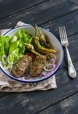 Αρνί kebab, πικάντικα ψημένα πιπέρια και φρέσκια πράσινη σαλάτα στο πιάτο σε μια σκοτεινή ξύλινη επιφάνεια Στοκ Φωτογραφία