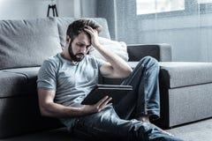 Αρνητικός ευχαριστημένος γενειοφόρος αρσενικός έχοντας τον πονοκέφαλο στοκ φωτογραφίες