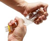 Αρπαγή δύο χεριών και πλαστικό μπουκάλι συστροφής Στοκ Εικόνες