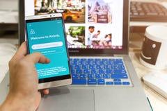 Αρρενωπή συσκευή που παρουσιάζει εφαρμογή Airbnb στην οθόνη Στοκ Φωτογραφίες