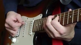 Αρσενικά δάχτυλα κινηματογραφήσεων σε πρώτο πλάνο που παίζουν σόλο στην ηλεκτρική κιθάρα απόθεμα βίντεο