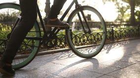 Αρσενικά απρόσωπα πόδια που περπατούν με το ποδήλατο στο στρωμένο ενεργό τρόπο ζωής οδικής κοντά επάνω πλάγιας όψης Άτομο στη μαύ απόθεμα βίντεο