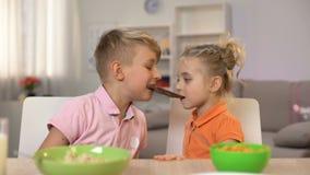 Αρσενικά και θηλυκά παιδιά που τρώνε τη σοκολάτα μαζί, αδελφός που μοιράζεται την αδελφή γλυκών απόθεμα βίντεο