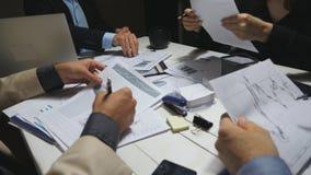 Αρσενικά και θηλυκά χέρια των συναδέλφων που εξετάζουν τις γραφικές παραστάσεις στο τέλος της εργάσιμης ημέρας Συνεδρίαση επιχειρ απόθεμα βίντεο