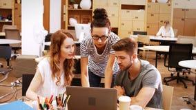 Αρσενικά και θηλυκά ανώτατα στελέχη επιχείρησης που συζητούν πέρα από το lap-top στο γραφείο τους απόθεμα βίντεο