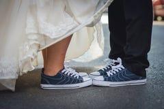Αρσενικά και θηλυκά πόδια στα πάνινα παπούτσια Νεόνυμφος νυφών γάμος Στοκ Φωτογραφίες