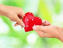 Αρσενικά και θηλυκά χέρια που κρατούν την κόκκινη καρδιά Στοκ φωτογραφία με δικαίωμα ελεύθερης χρήσης