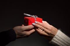 Αρσενικά και θηλυκά χέρια που περνούν το διακοσμημένο δώρο στο Μαύρο Στοκ Φωτογραφίες