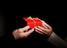 Αρσενικά και θηλυκά χέρια που περνούν το διακοσμημένο δώρο στο Μαύρο Στοκ Εικόνες