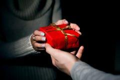 Αρσενικά και θηλυκά χέρια που περνούν το διακοσμημένο δώρο Στοκ Εικόνες