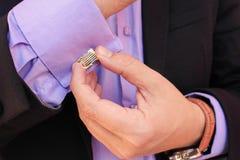 Αρσενικά μανικετόκουμπα κουμπιών χεριών στο πορφυρό πουκάμισο Στοκ Εικόνες