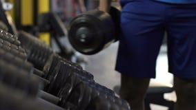 Αρσενικά που παίρνουν τους βαριούς αλτήρες από τη στάση στη γυμναστική, φυσικό workout, ανύψωση βάρους φιλμ μικρού μήκους